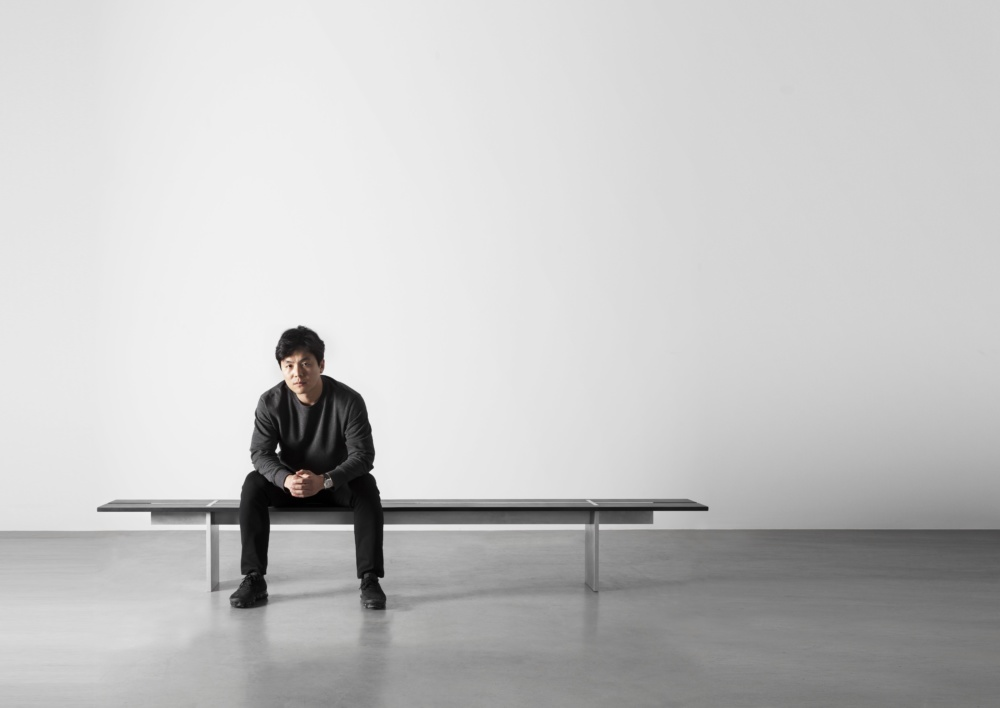 Wonmin Park sitting on a bench from his Plain Cuts collection at the Carpenter's Workshop Gallery