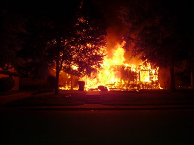 A wood-frame building is ravaged by fire. (Courtesy U.S. Air Force)