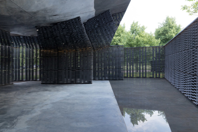 A mirrored canopy reflects the scene in the pavilion, while a reflecting pool bounces in light from above.