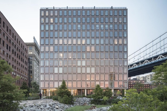 Exterior photo of 12-story square building next to park and Manhattan Bridge, an Alloy project