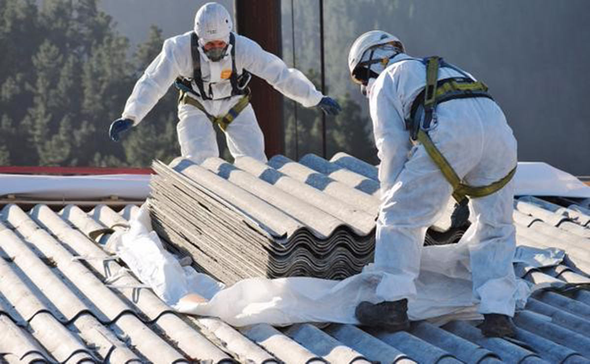 A photo of men working with asbestos tiles on a roof