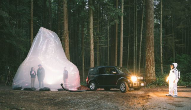 The Gas Trap is a 25-foot-wide kinetic sculpture and stage hybrid where performers are seemingly trapped within a volume inflated by the tailpipe of an SUV.