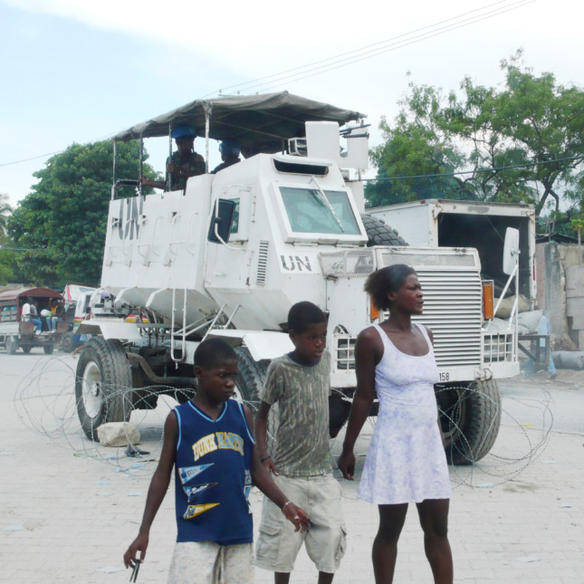 In Port-au-Prince, Haiti, people stand in front of an armored personnel carrier (APC) deployed in the UN-MINUSTAH peacekeeping mission. This APC has been surrounded by barbed wire and placed on wheel chocks, converting it, at least temporarily, from a vehicle to a quasi-architectural technology—a mobile tower.