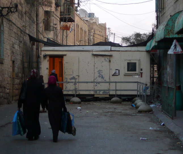A checkpoint manned by Israeli Defense Force soldiers blocking the entrance to Shuhada Street, a formerly vital Palestinian market street in the Old City of Hebron.