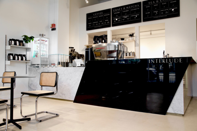 The owner mixed midcentury modern style with the simplicity of Danish design by bringing in pieces like Marcel Breuer's Cesca Chairs and the Neu Table by HAY. The focal point of the space is the dramatic L-shaped cafe counter with marble and granite from Arena Stone Products in New Jersey.