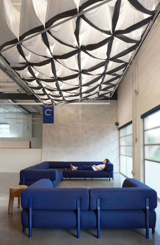 The Pillow Cloud by SAW incorporates Casper's own pillowcases and floats above the main common space, softening sound and light for all-hands meetings or break-out groups. A custom sliding door, also made out of perforated steel, masks industrial shelving and storage areas while still offering a hint of what lies beyond.