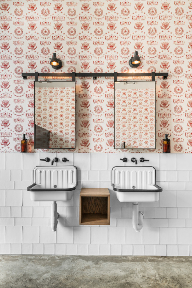 Farmhouse sinks and custom wallpaper in a graphic, Texas-themed pattern complement glazed tile in each restroom.