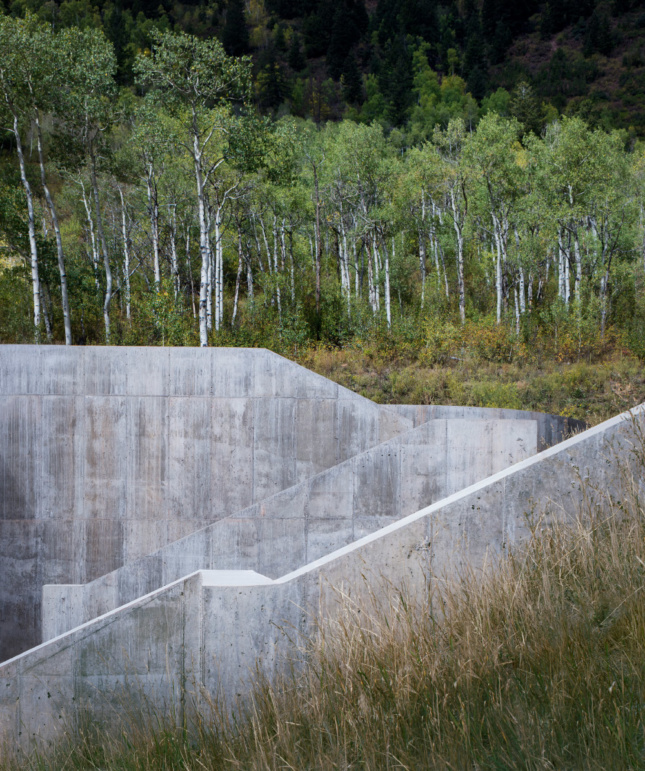 Madderlake constructed a concrete impact wall that's sculpted into the hillside. It provides additional support for the steel-framed structure in case of an avalanche.