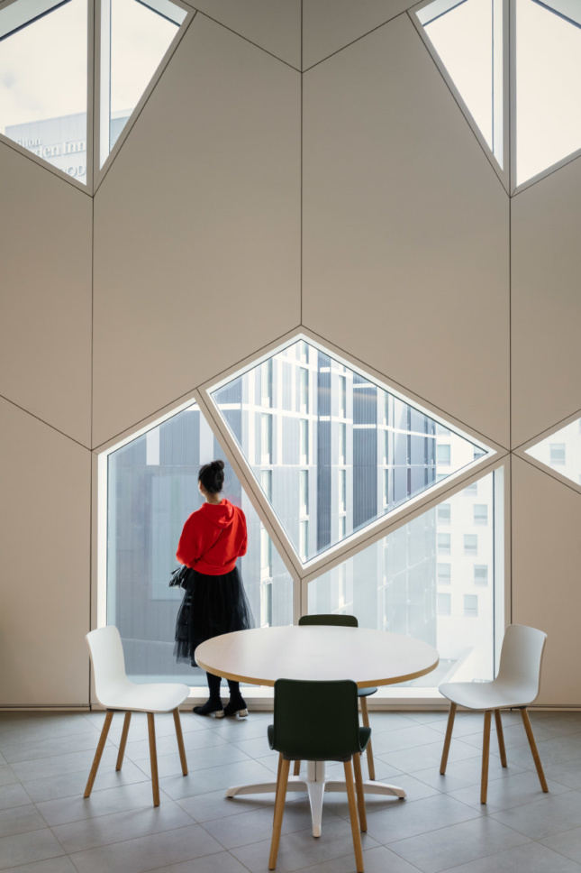 A library patron looking up from a lounge table. The panel-to-glass density of the facade was adjusted to cut strategic views into the building.