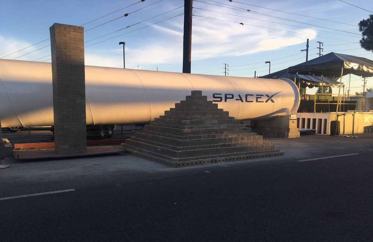 A pile of Boring Company-made bricks in front of a Hyperloop tube.