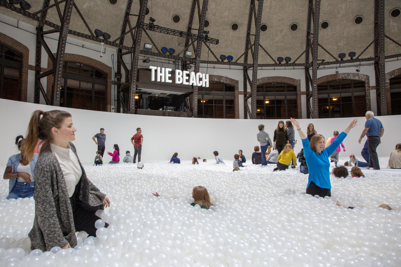 Photo of a white ball pit and visitors