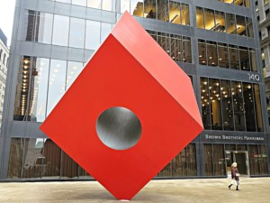 A large red cube with a hole in it in front of 140 broadway