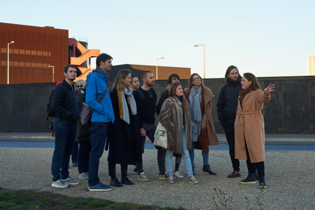 Photo of a group of people standing outside and looking at something off-camera