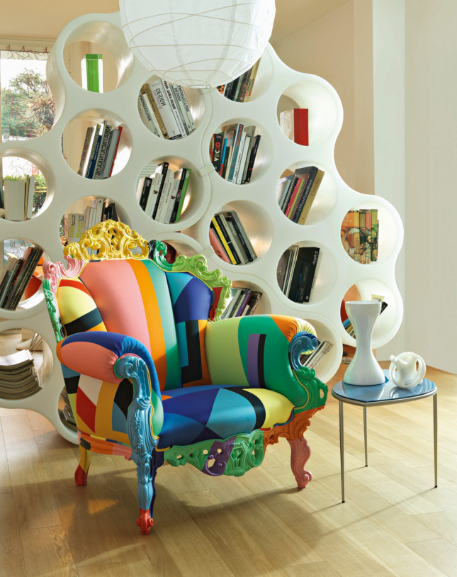 Photo of a multicolored Proust armchair in front of a bookshelf