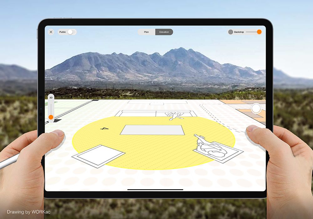 Hands hold up an iPad Pro in front of a mountain seen where a scale CAD drawing is projected.