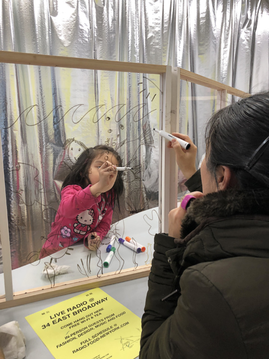 A child and an an adult draw with dry-erase markers on opposite sides of a glass pane.