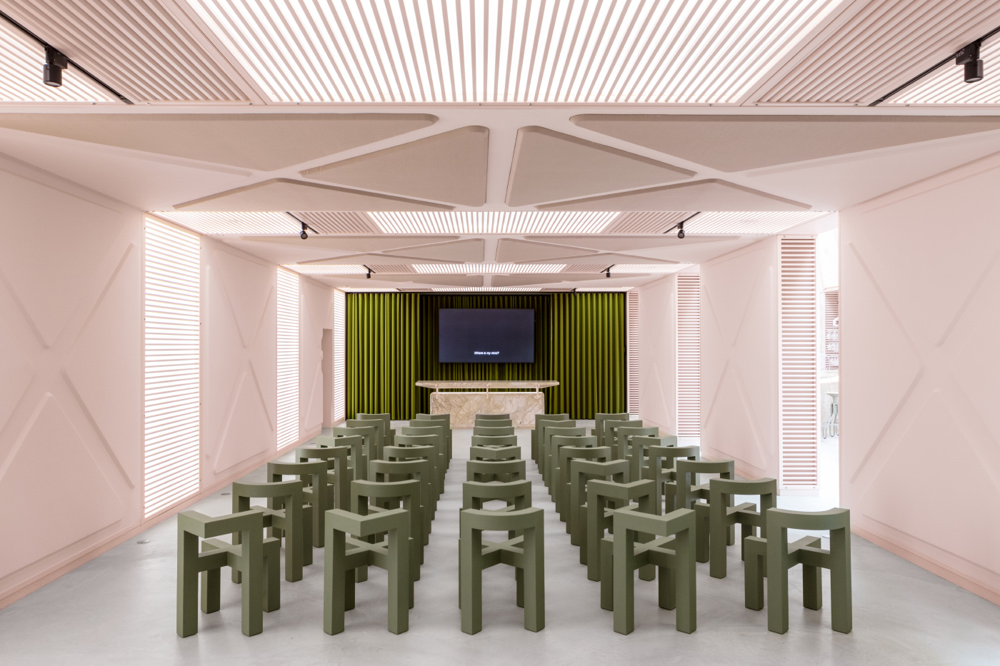 A pink conference room with green chairs