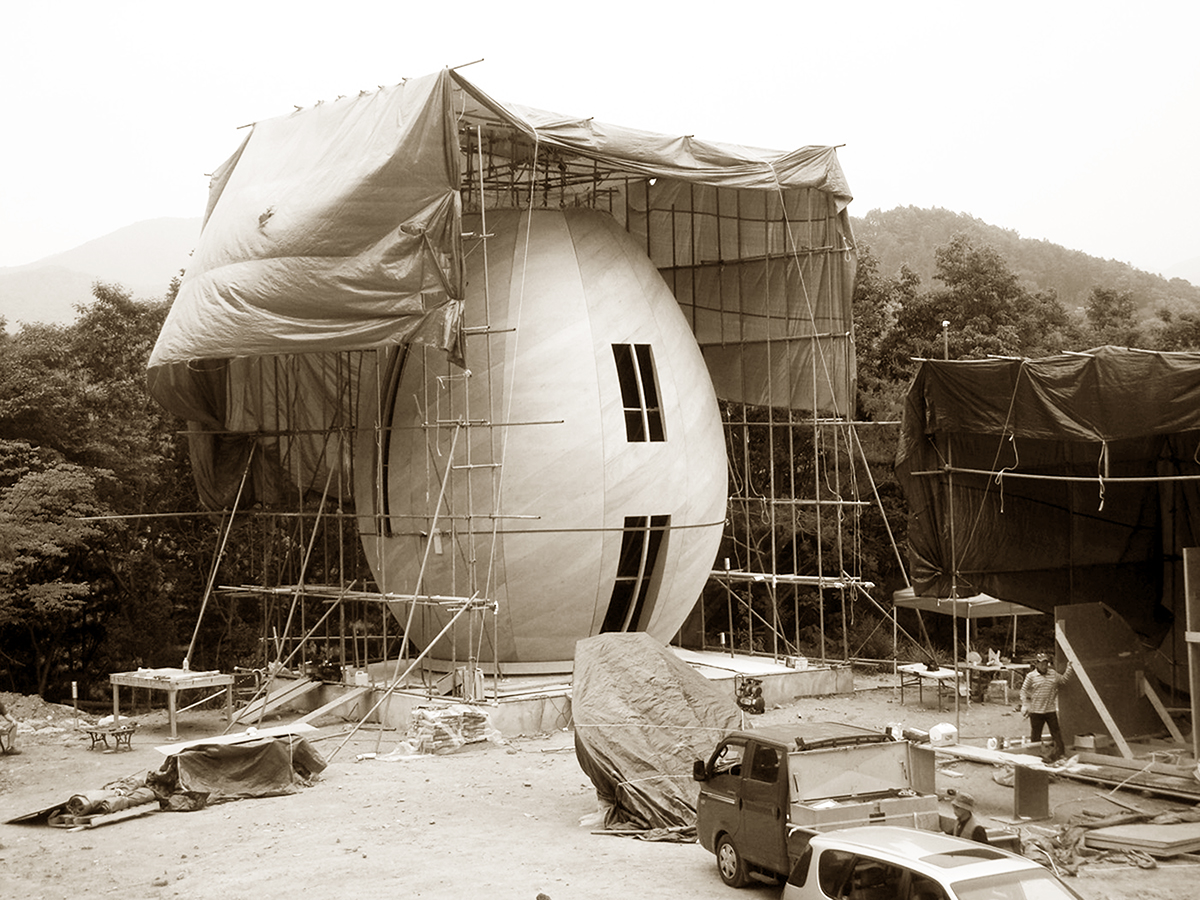 Sepia photo of an egg-shaped building under construction