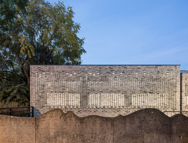 Photo of a concrete wall in front of a brick facade