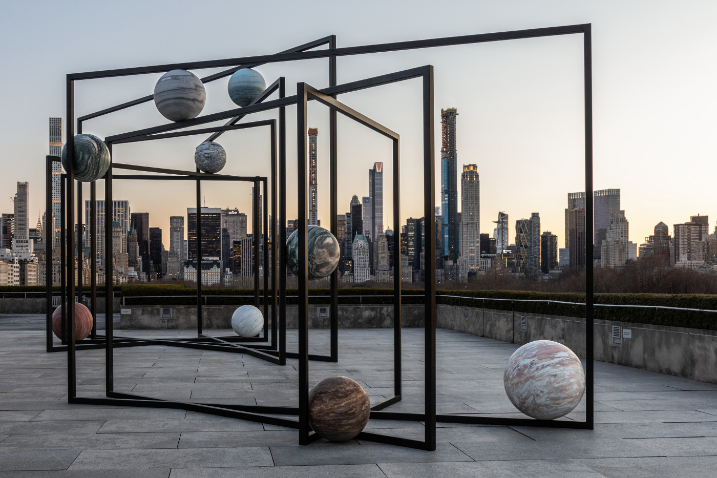 Photo of large stone spheres of different colors, suspended in black steel frames, against the Manhattan skyline