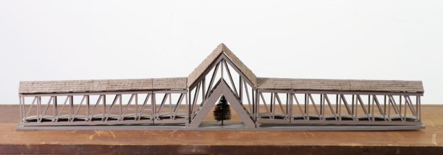 Photo of a model of a bridge spanning over a tree