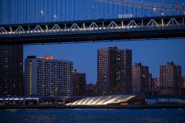 A view of the Manhattan Bridge at night with a lit-up park below