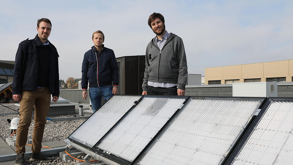 Photo of three people standing on a roof by solar panels