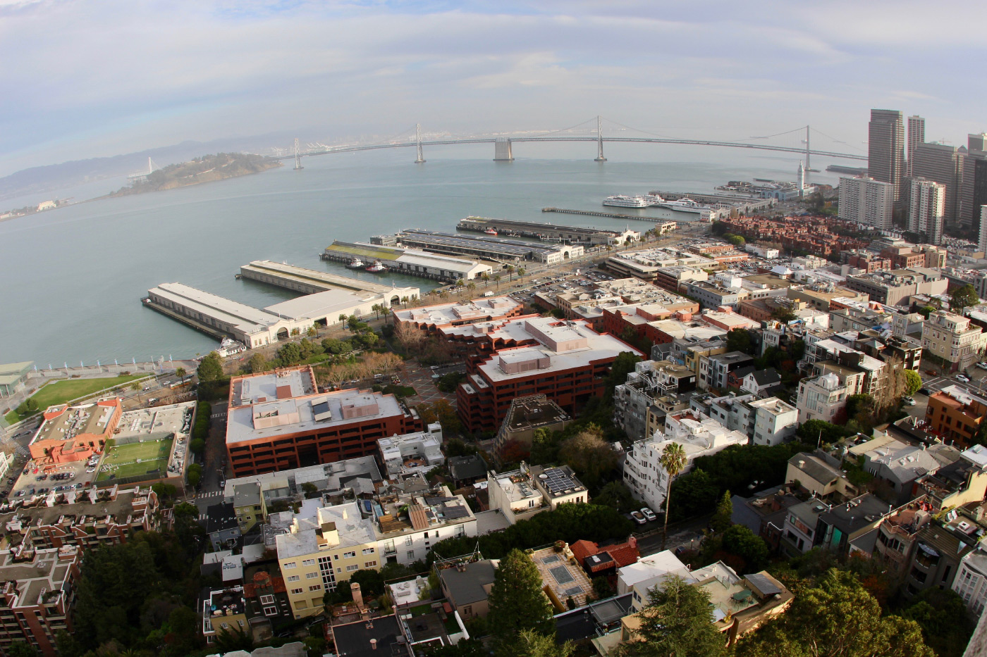 An aerial photo of a bay and waterfront neighborhood spanned by a bridge