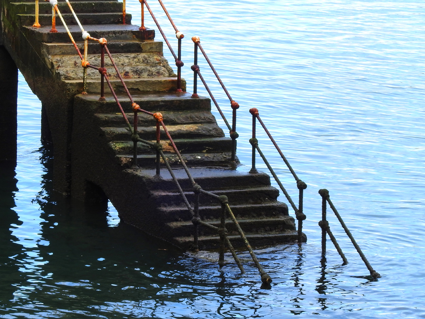 Photo of a set of worn and weathered stairs descending into water