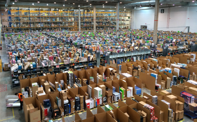 Photo of rows upon rows of cardboard boxes being packed in a warehouse