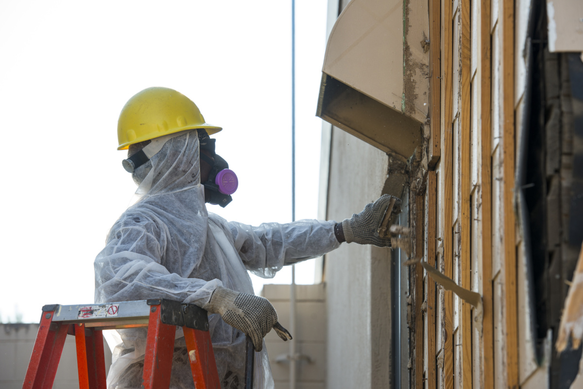 Photo of worker removing asbestos from building wall before demolition