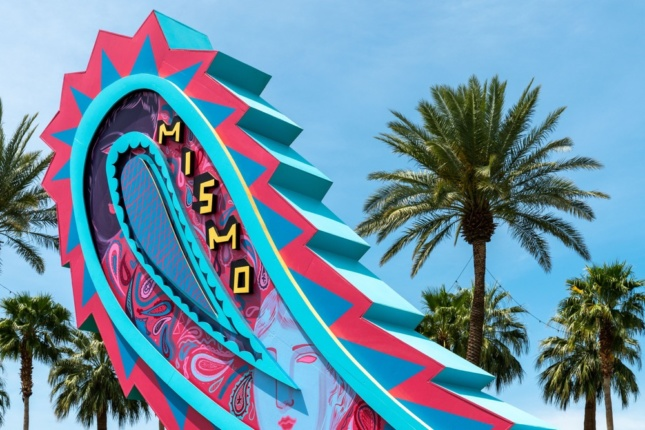 Photo of a brightly colored sign in the desert in the shape of a paisley swirl