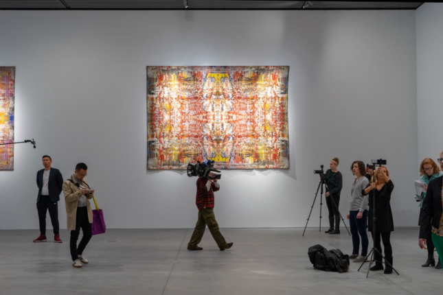 A tapestry in a white gallery