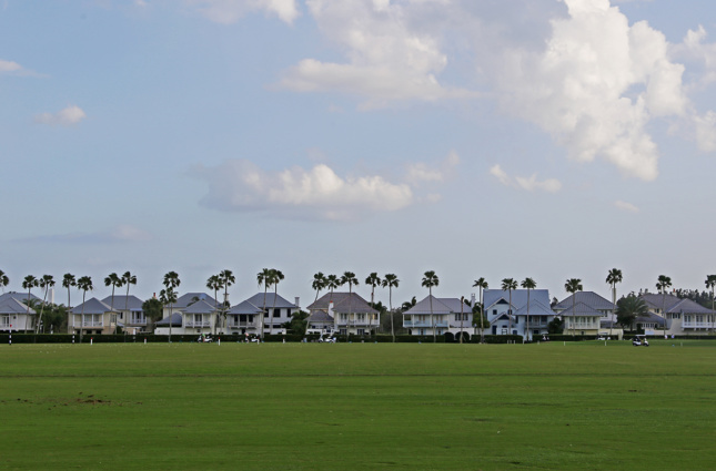 Photo of a row of large houses with a golf course in front of them