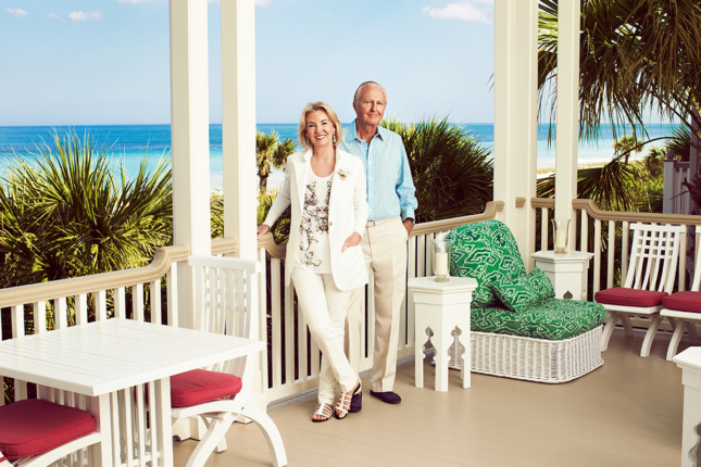 Photo of two older white people standing on a porch overlooking the ocean