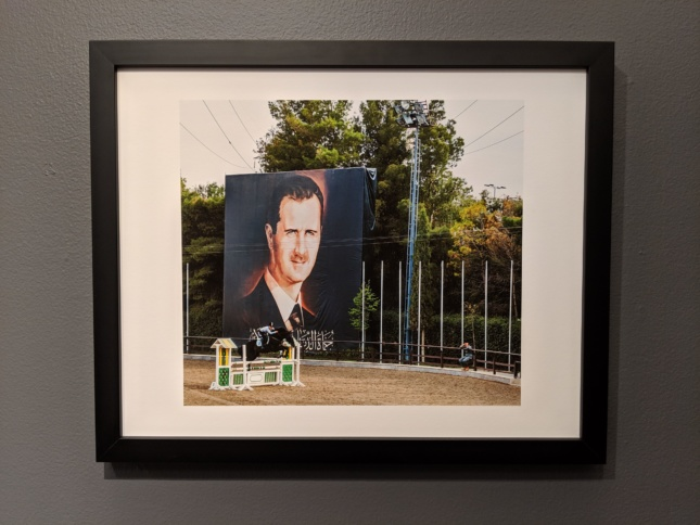 Photo of a photo of an outdoor space with a large mural of Bashar al-Assad