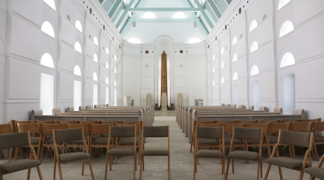 Photo of folding chairs arranged in the interior of a white light-filled chapel