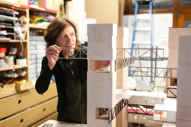 Photo of a woman sliding a piece into an architectural model