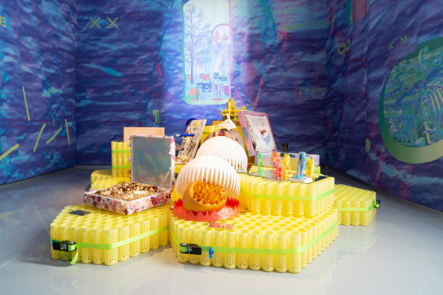 Photo of plastic pedestals with small objects on top in a bluish-purple room