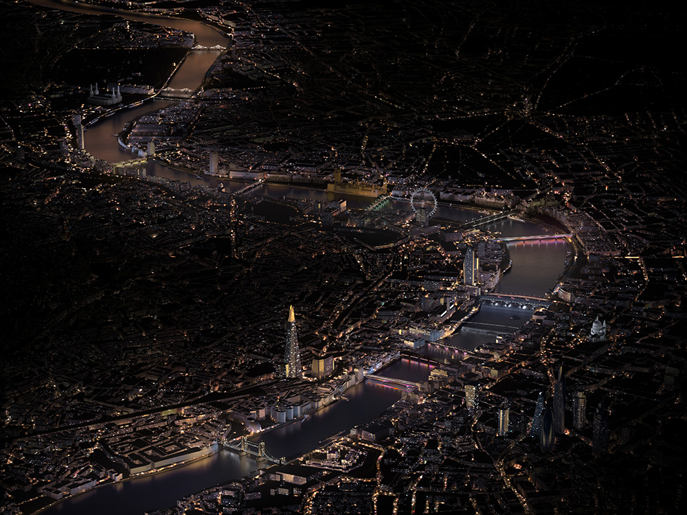 A bird's eye view of London with bridges across the Thames lit up colorfully
