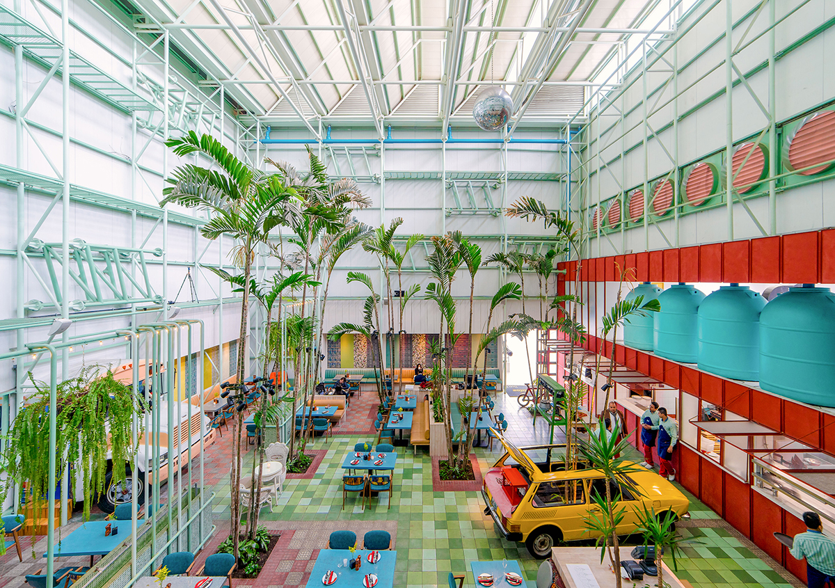Photo of a room with a very high ceiling with bright colors, palm trees, and restaurant seating inside