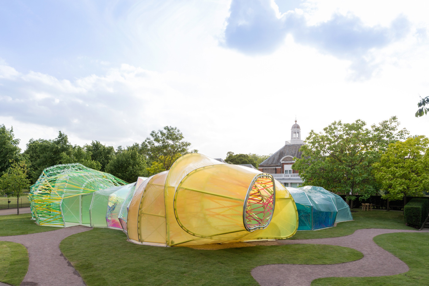 Photo of a large, multicolored fabric installation on an open lawn