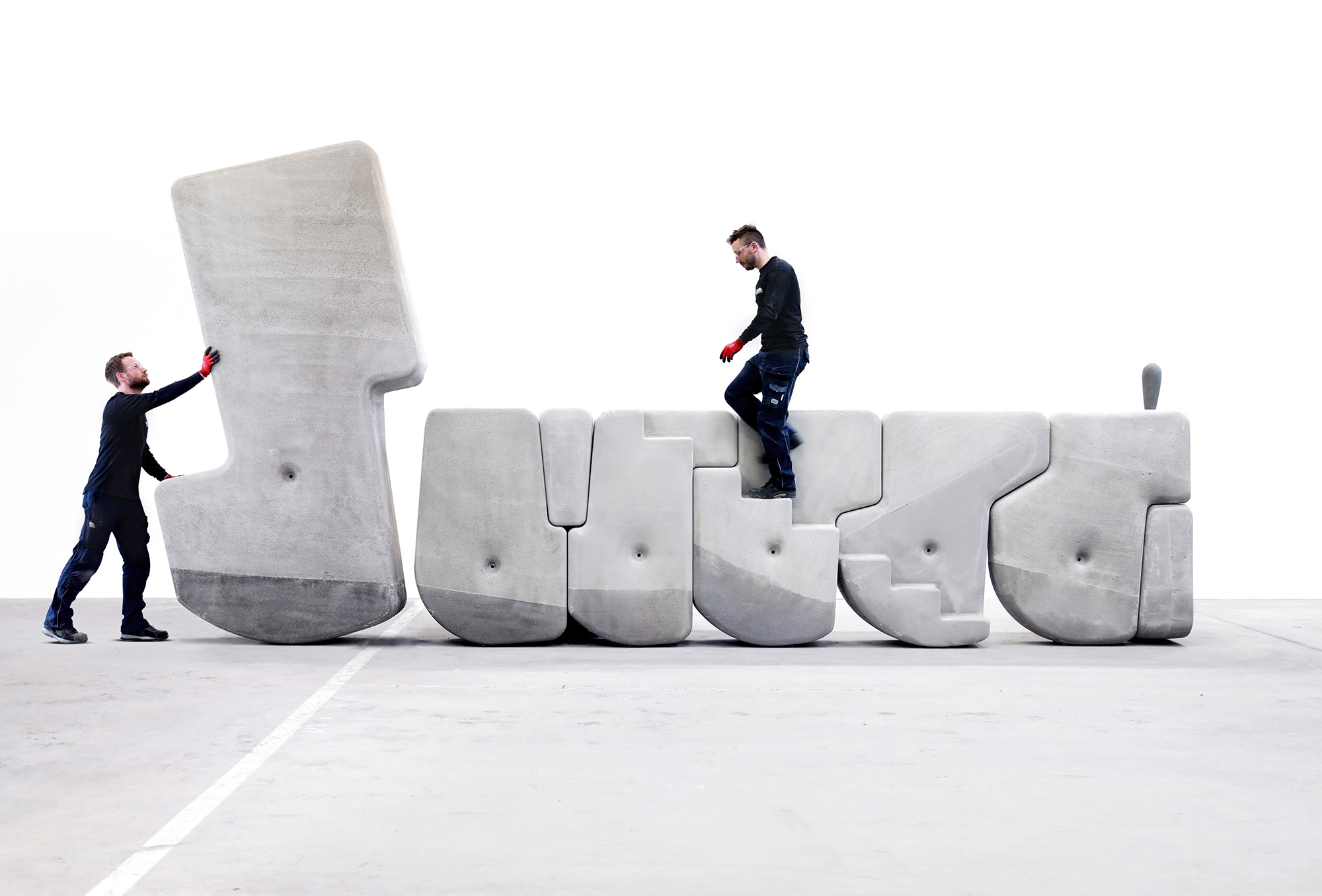 Photo of a man climbing concrete steps and another rocking a large concrete object