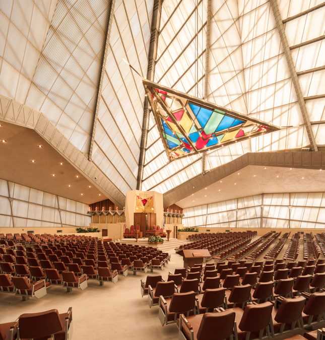 An interior photo of a temple, with a large stained glass triangle and glass walls extending upwards