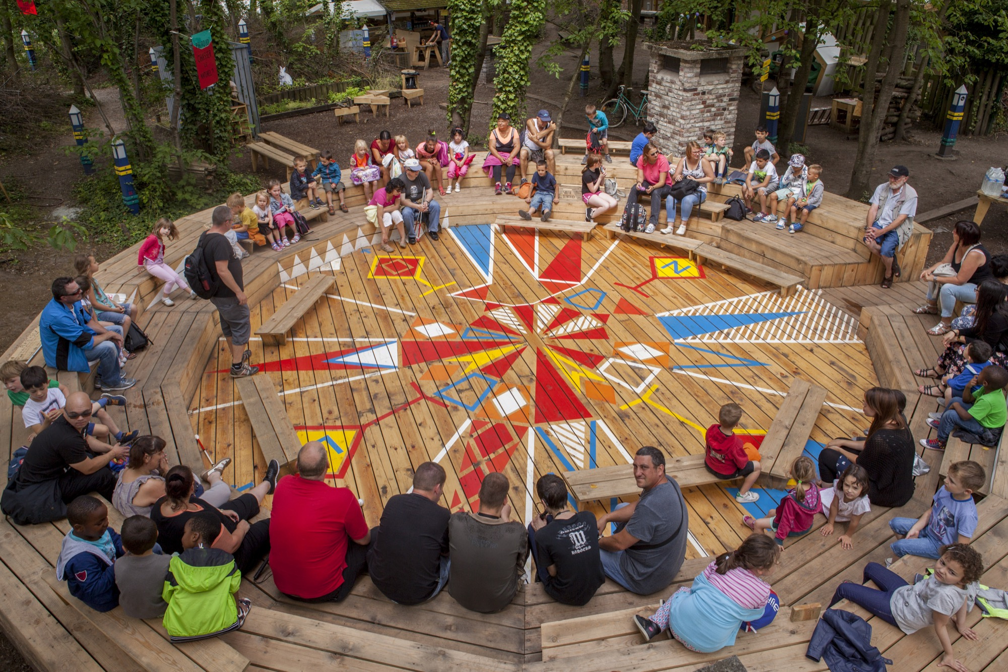 Photo of people sitting in a round wood seating arrangement