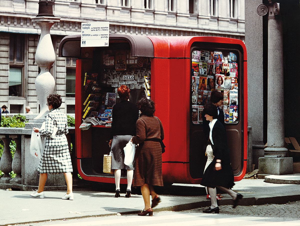 Photograph of a rounded red kiosk selling magazines on the street with people walking by it