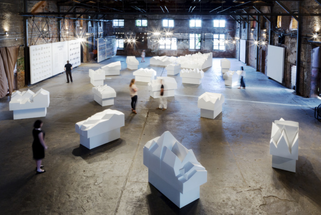 Installation of white gabled house models in warehouse gallery