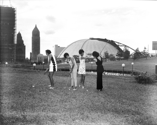 Black and white photo of four people playing golf in downtown Pittsburgh