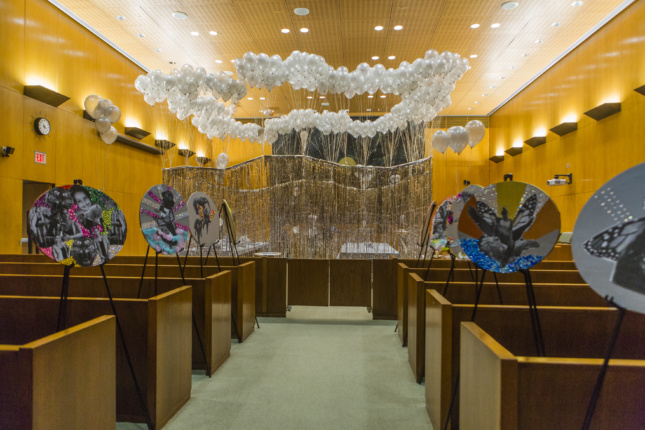 Photo of installation inside courtroom with art pieces hanging