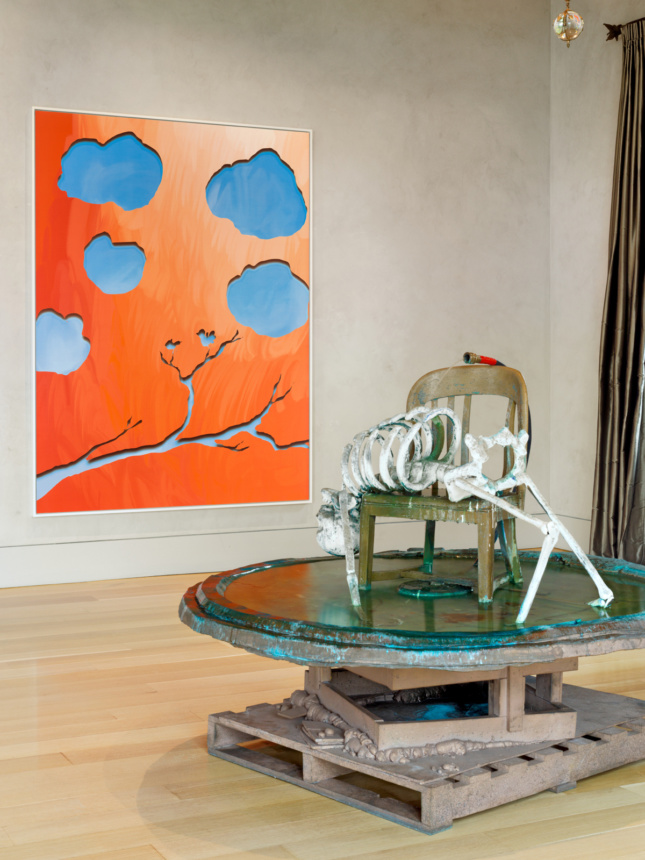 A sculpture of wooden palettes topped with a fountain props up a skeleton on a chair, with a garden hose on top. In the background a painting of a tree black and clouds—the sky is orange and the clouds and branch are produced in negative in blue.